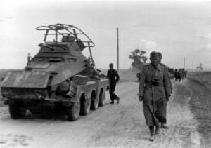 General Schmidt marschiert zu Fuß neben einem Sonderkraftfahrzeug 231